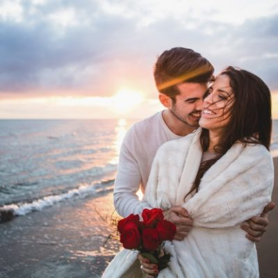 smiling-couple-walking-on-the-beach-with-a-bouquet-of-roses-at-sunset_23-2147595923